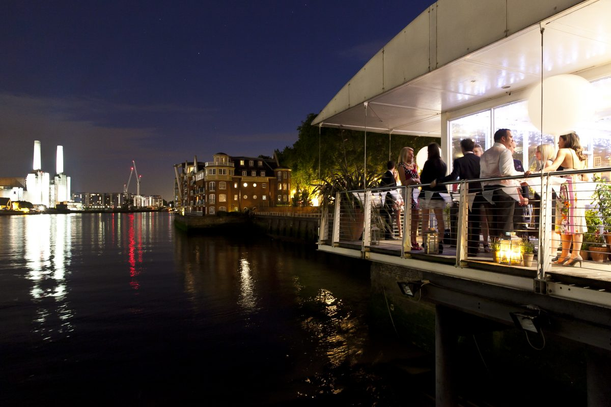 nighttime riverside party venue with terrace